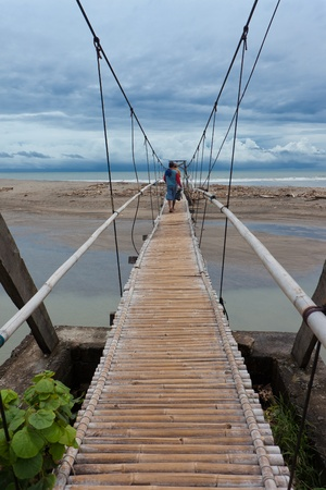 bridge over water: Men walking on suspension bridge over small river leading to the sea in Bali.