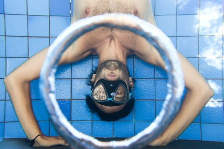 Man making bubble rings underwater in pool photo