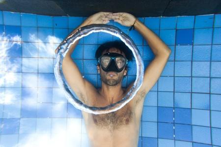 subaquatic: Man making bubble rings underwater in pool