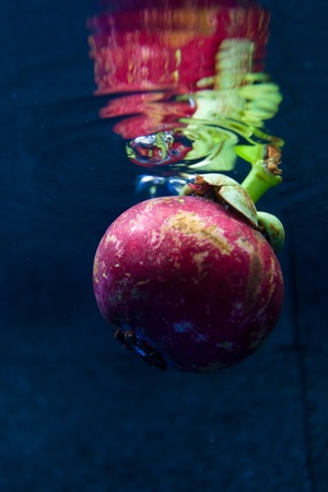 Fresh red mangostin underwater with natural light at surface