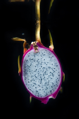 Sliced dragon fruit in water on black background photo