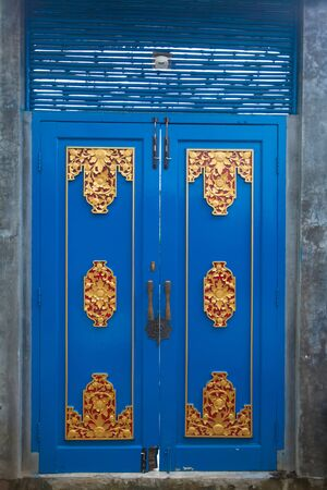 Blue wooden door decorated with red and gold painted carvings Stock Photo - 13678034