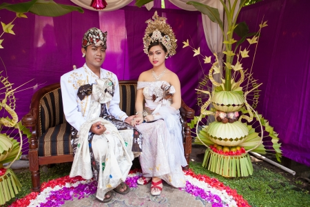 celebratation: BALI - FEBRUARY 11. Couple enacting wedding scene in preparation for religious ceremony on February 11, 2012 in Bali, Indonesia. Most Balinese get married in their early 20s. Stock Photo