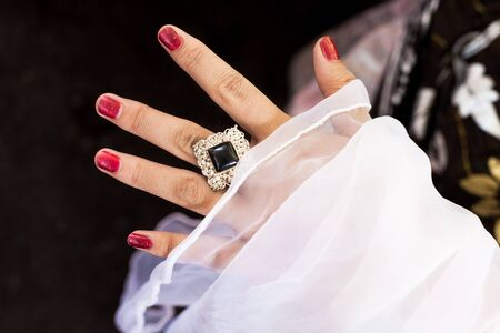 Bride shows her large ring on her finger with white veil on hand