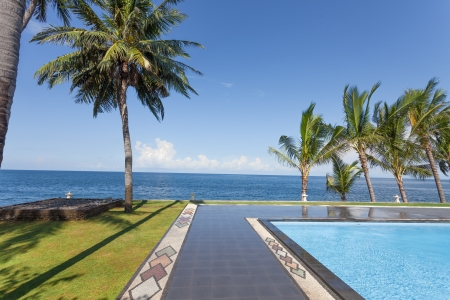 swimming pool and palm trees on seaside in Bali, Indonesia Stock Photo