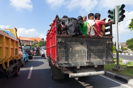 afford: BALI - FEBRUARY 13. Workers travel by pickup truck on February 13, 2012 in Bali, Indonesia. Most workers cannot afford their own means of transport. Editorial