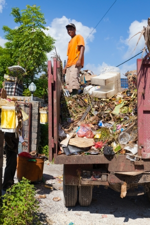 BALI - FEBRUARY 13. Young man collecting village waste in truck on February 13, 2012 in Bali, Indonesia. Waste management is difficult to tackle in fast developing countries such as Indonesia.
