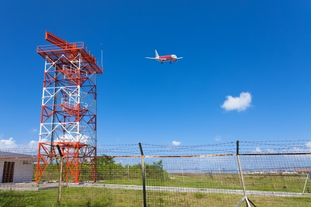 Red and white metal radar tower in airport area with plane landing