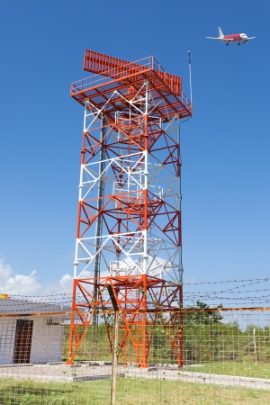 Red and white metal radar tower in airport area with plane landing Stock Photo - 13678095