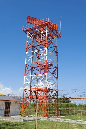 Red and white metal radar tower in airport area photo