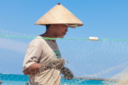 BALI - FEBRUARY 13. Fishermen cleaning nets on beach on February 13, 2012 in Bali, Indonesia. Fisheries Minister Fadel Muhammad said Indonesia set to become worlds largest fish producer in 2015.
