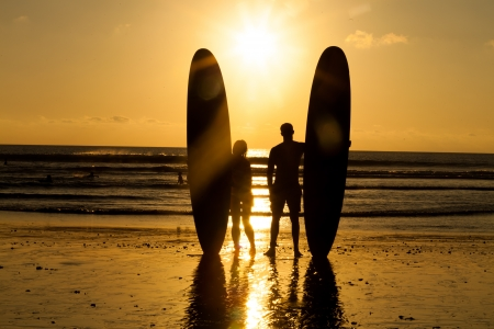 Surfer couple in silhouette holding long surf boards at sunset on tropical beach photo