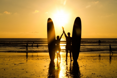longboard: Surfer couple in silhouette holding long surf boards at sunset on tropical beach