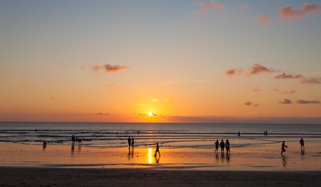 People enjoying sunset on Kuta beach in Bali, Indonesia Stock Photo - 13677913