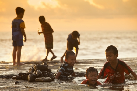 kids playing by the sea in tanah lot bali