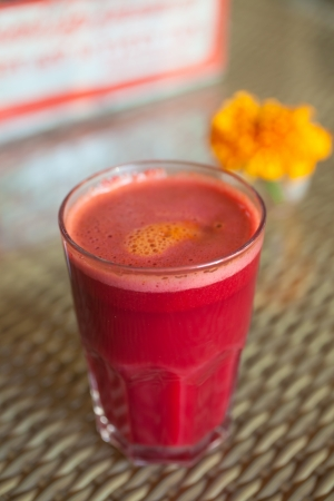 Full glass of beetroot and carrot juice decorated with flower in vegetarian restaurant