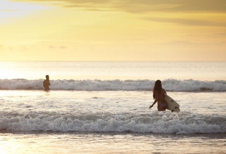 Beautiful asian woman in bikini in the surf with board Editorial