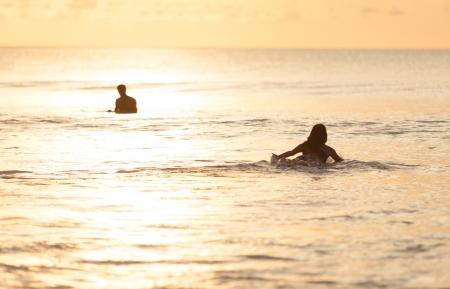 Beautiful asian woman swimming on surfboard photo