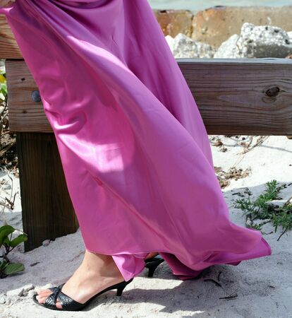 tacones negros: Vestido de sat�n rosa de una mujer y tacones de negro en una playa de arena
