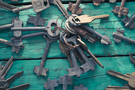 four objects: Old keys on a green wooden table Stock Photo