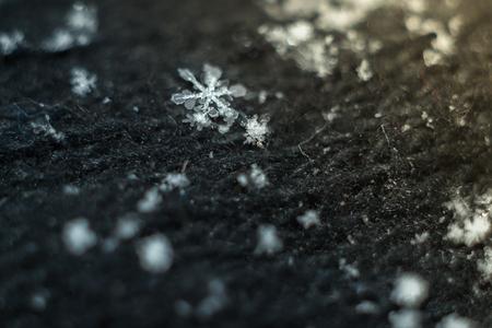 Macro snowflake on a black background cloth