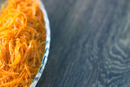 Fresh carrot salad on a wooden background