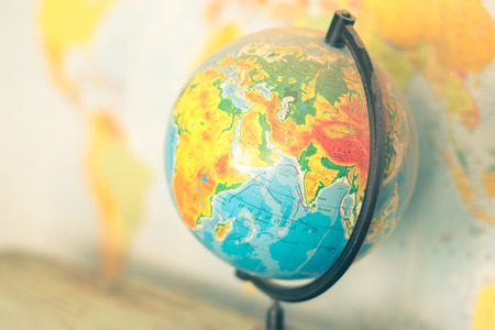 Globe on a blurred background of the political map of the world