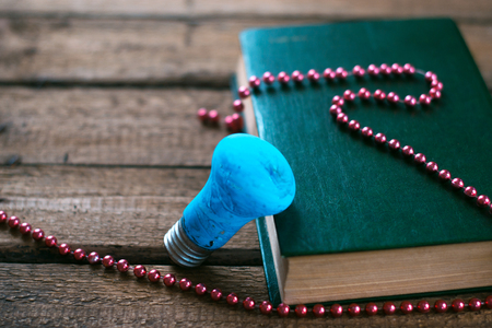 correspondencia: Glass lamp on the wooden table near the book with beads.