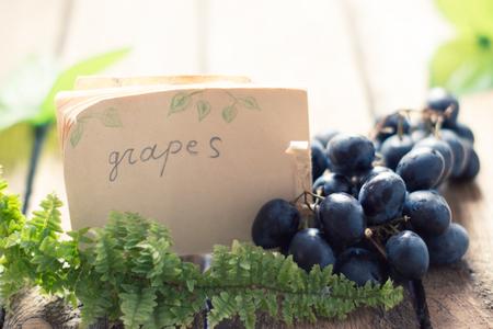Druiven op een houten tafel met een tag Stockfoto - 74905902