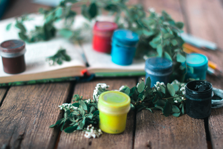Jar of paint on a wooden background with leaves of plants