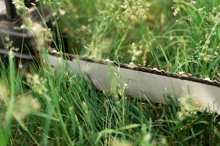 Power saw on green grass on blur background