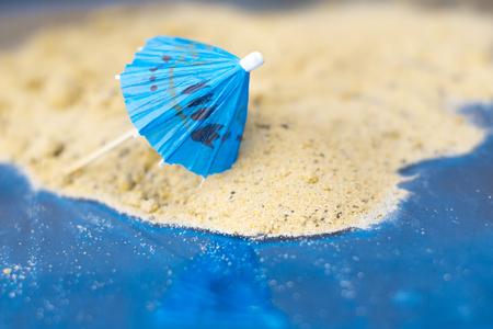 aridness: Cocktail umbrellas on the sand of a sunny beach