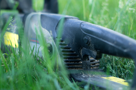 Electric saw on green grass with blurred background
