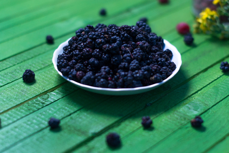 Fresh blackberries on a wooden green background