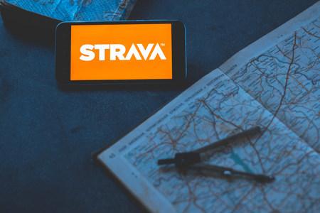 Strava application on the phone on a dark background with map
