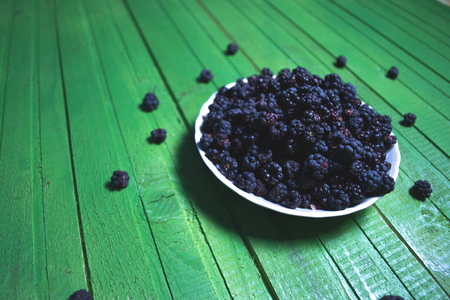 shiny black: Fresh blackberries on a wooden green background