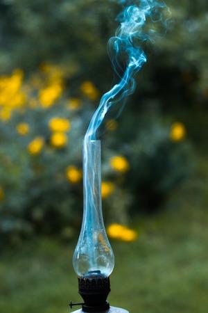 extinguishing: A smoking old kerosene lamp on a green grass