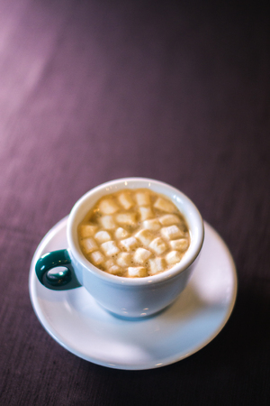Coffee in cafe with marshmallow with blurred background
