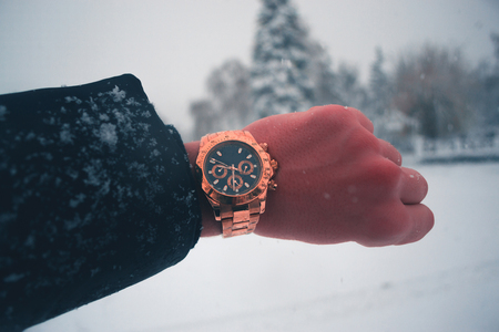 A mans hand with a gilded clock against a snowfall in the town Stock Photo