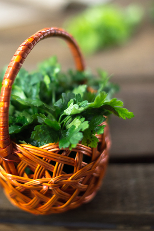 Parsley in a basket on a wooden background