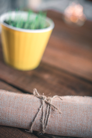 Pot in a pot on a wooden background with burlap-bound
