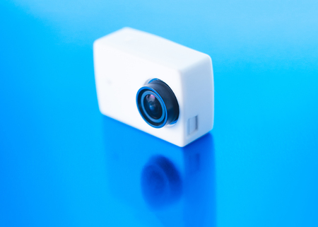 Action camera on a blue glossy background