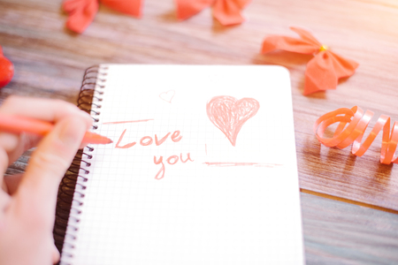 A man writes a text on a white sheet i love you