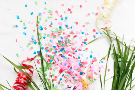 Confetti on a white background isolate with stems of green grass. Imagens