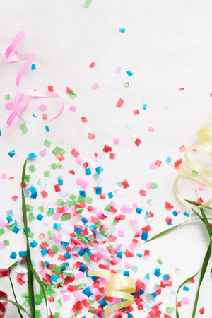 Confetti on a white background isolate with stems of green grass. Stock Photo