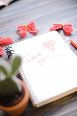 Inscription I love you on a white notepad on a wooden background.