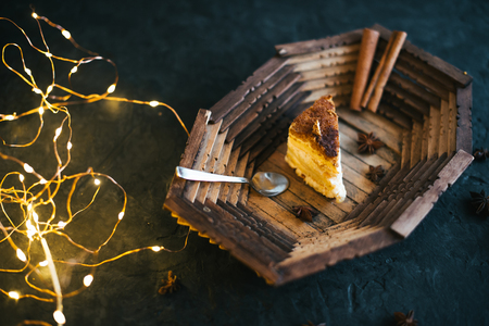Cake on a wooden tray on a black matte background. Stock Photo
