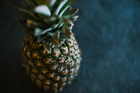 Pineapple on a black matte cement background.