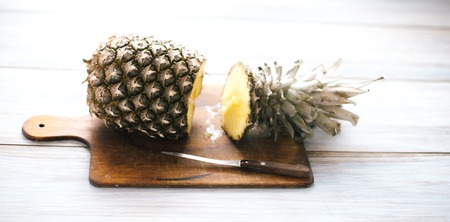 Ripe bisected ripe pineapple on a wooden background.