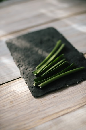 Sliced green stems on a black kitchen board. Stock Photo